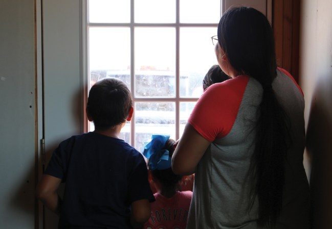 Navajo family looking out a window