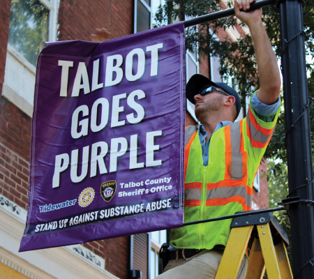 Easton Utilities worker hanging a Talbot Goes Purple banner
