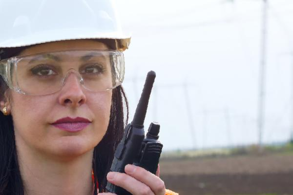 woman in hard hat and transmission lines