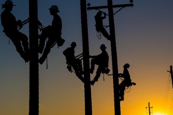 lineworkers on utility poles at sunset