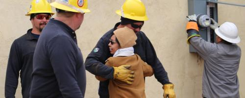 Navajo Nation resident hugs volunteer lineworker crews participating in Light Up Navajo in 2019