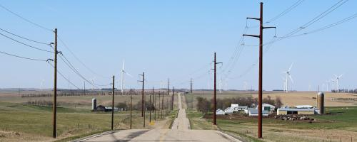 Transmission towers over a field and dirt road - Heartland